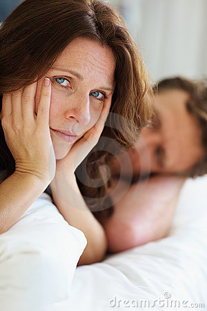 Unhappy woman lying besides husband in bed