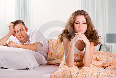 Unhappy young couple in bedroom