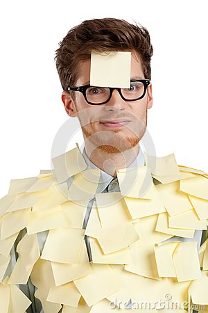 Unhappy young man with a sticky note on his face, covered with stickers