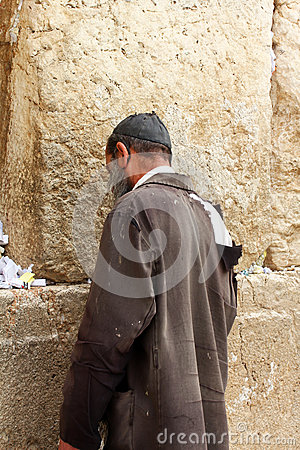 Unidentified poor man praying at the Wailing wall Editorial Stock Image