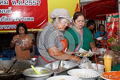 An unidentified Thai people sells pad thai on night market wall street.