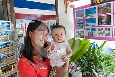 An unidentified Thai woman with cute baby at work in travel agent office in Phang Nga province Editorial Photography
