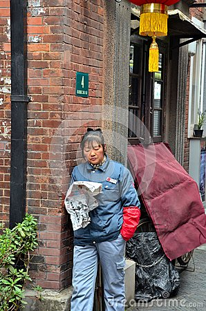 Street cleaner reads newspaper Shanghai China Editorial Stock Photo