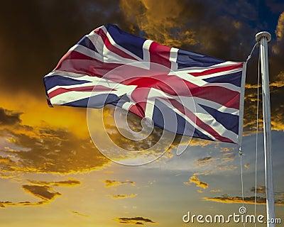 Union Jack on flagpole under dark brooding sky.