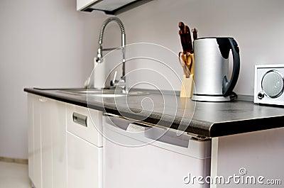 Unità bianca moderna della cucina con il rubinetto di miscelatore il