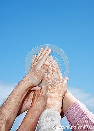 Unité - un groupe de main a augmenté contre le ciel