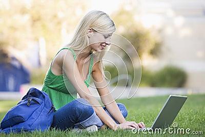 Universitaire student die laptop buiten met behulp van