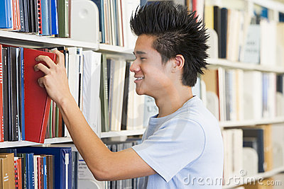 University student selecting book from library she