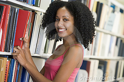 University student selecting book from library