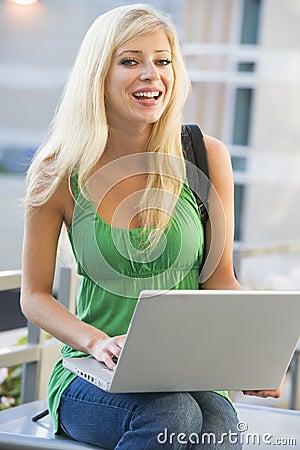 University student using laptop outside