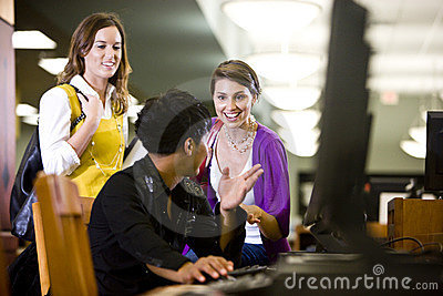 University students conversing by library computer