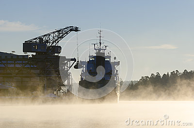 Unloading bulk freighter ship cold morning Editorial Image