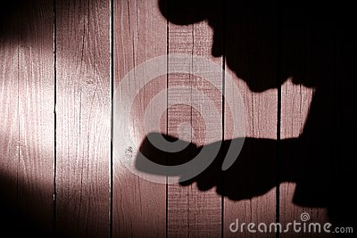 Unrecognizable burglar with  flashlight  in shadow on wood backg