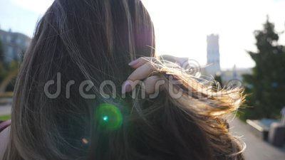 Unrecognizable dark haired woman standing at urban street and straightening hair. Girl standing at city environment with. Bright sunlight at background. Lady stock footage