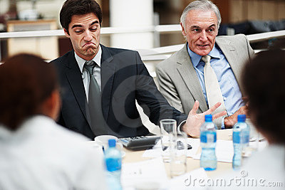 Unsatisfied business man sitting with team