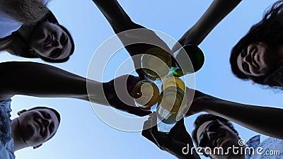 Untere Ansicht: Fünf Freunde klammern sich auf der Sommerparty mit Bierflaschen gegen den Himmel stock video