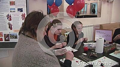 Unterrichtende Kinder der Frau, wie man handgemachte Anhänger bei Tisch macht liebhaberei kreation feiertag stock footage