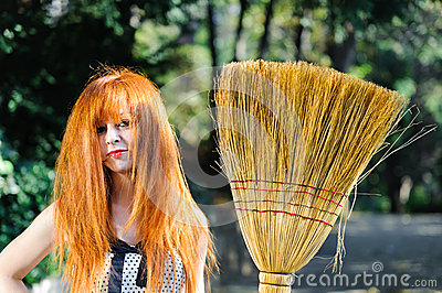 Untidy red haired cute young girl holding broom