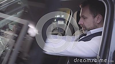 Uomino caucasico adulto seduto al sedile del conducente e soddisfatto dell'espressione del volto Imprenditore elegante stock footage