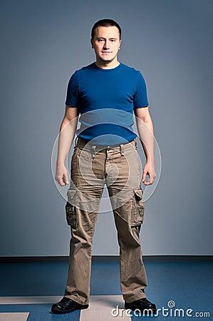 Uomo adulto che si leva in piedi con un fronte di smirk