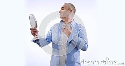 Uomo anziano che controlla la faccia nello specchio Isolato su bianco stock footage