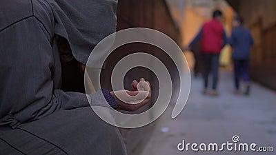 Uomo anziano povero con il bastone in djellaba che elemosina il dotation con la mano allungata sulla via vicino alla moschea in F stock footage