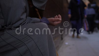 Uomo anziano povero con il bastone in djellaba che elemosina il dotation con la mano allungata sulla via vicino alla moschea in F video d archivio