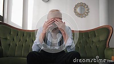 Uomo anziano solitario con barba e occhiali per la vista soffre di depressione e emicrania con mani nella testa mentre stock footage