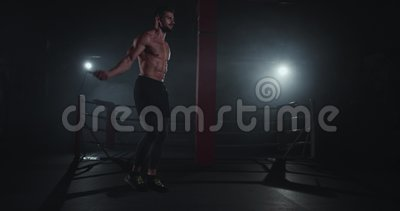 Uomo atletico carismatico in una classe di forma croce scura con un corpo nudo che salta sulla corda suda e video d archivio
