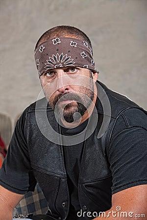 Uomo barbuto serio in maglia di cuoio
