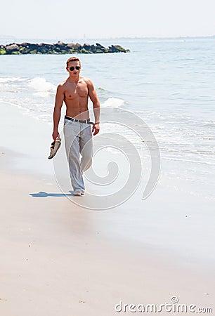 Uomo bello che cammina sulla spiaggia