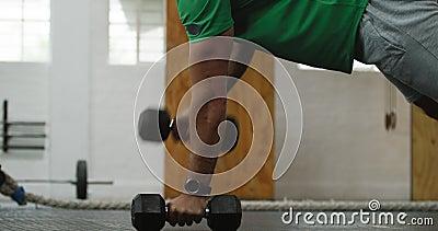 Uomo caucasico atletico dalla vista laterale che solleva pesi alternati video d archivio