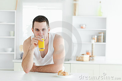 Uomo che beve il succo di arancia