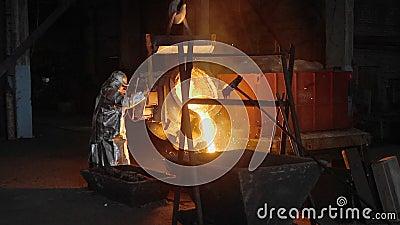 Uomo che lavora con il metallo liquido in fabbrica La fabbrica del metallo scintilla video d archivio