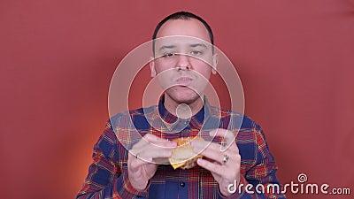 Uomo che mangia un hamburger ripresa a distanza ravvicinata Mangia di cibo veloce video d archivio
