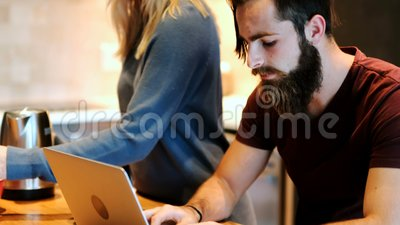 Uomo che per mezzo del computer portatile mentre donna che prepara caffè 4k archivi video