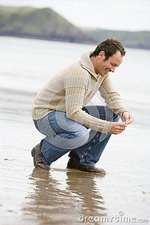 Uomo che si accovaccia sulla spiaggia