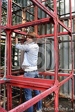 Uomo che si tira in su sulle costruzioni del metallo