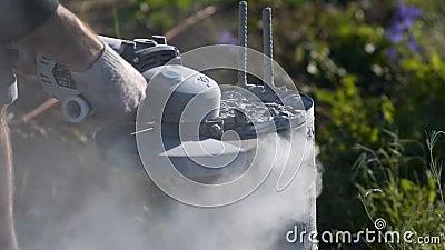 Uomo che taglia una colonna concreta Scintille della costruzione della polvere del calcestruzzo e del metallo stock footage