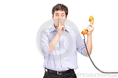 Uomo che tiene un telefono e che gesturing silenzio