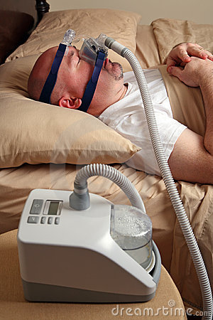 Uomo con il apnea di sonno per mezzo di una macchina di CPAP
