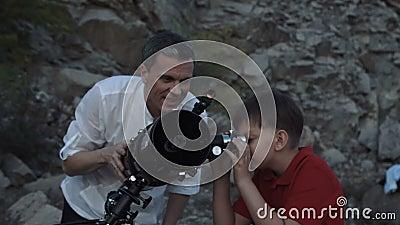 Uomo con il ragazzo che per mezzo del telescopio stock footage