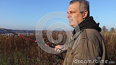 Uomo con la canna da pesca vicino al lago archivi video