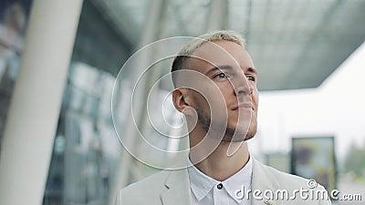 Uomo d'affari attraente biondo felice che cammina fuori vicino al grande edificio per uffici e che guarda intorno Uomo che sembra archivi video
