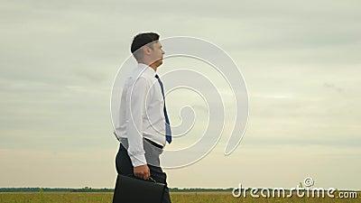 Uomo d'affari in camicia bianca in legame blu con i passaggi neri della cartella attraverso un parco per una riunione importante  stock footage