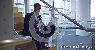 Uomo d'affari che utilizza computer portatile sulle scale nell'ufficio 4k video d archivio