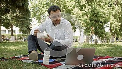 Uomo d'affari dei pantaloni a vita bassa che beve una tazza di caffè nel caffè della città durante il tempo del pranzo Sta lavora stock footage