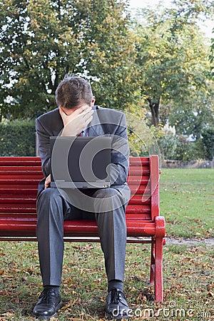Uomo d affari faticoso con il computer portatile