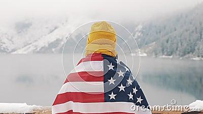 Uomo del viaggiatore con la bandiera della condizione dell'America nelle montagne innevate vicino al bello lago Viandante che esa stock footage