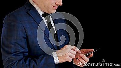 Uomo dell'uomo d'affari negli impianti del vestito sul suo smartphone, mostrante sorriso Le dita toccano il touch screen per scri video d archivio
